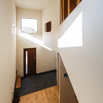 <p> 2階から玄関をみる: 右手奥の開口部は、和室の窓となっています </p>