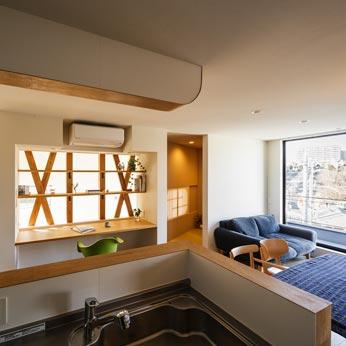 <p> キッチンから書斎・吹き抜け方面をみる: LDKや階下まで、つねに家族の気配を感じながら家事をすることができるキッチンの配置です </p>