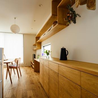 <p> キッチンの収納と飾り棚: 天然木の表情を大切にしました </p>