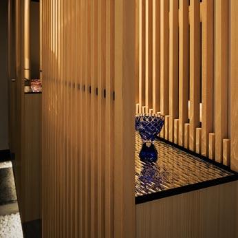 <p> 格子のダブルスクリーンの間にはウォーターミラーの飾り棚が設えられ、そこに職人業の江戸切子のちょこが飾られています </p>