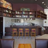 <p> キッチンをのぞむ: オープンカウンターのキッチン上部にも本棚が </p>