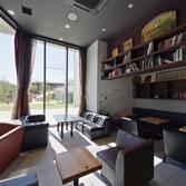 <p> 店内から外部を見通す: 新しく整備された東灘図書館の緑を借景としています </p>