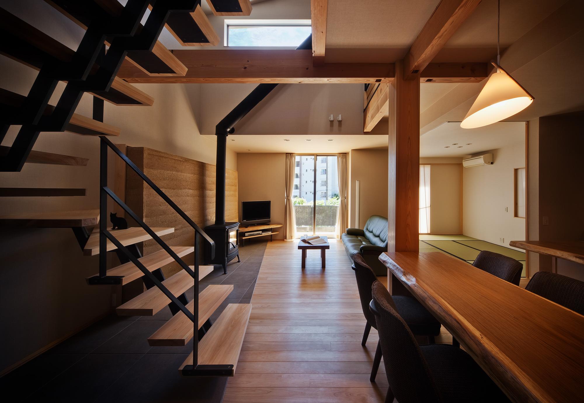 ダイニングよりリビングを見る: 玄関からダイニング、リビングに渡ってタイル貼りの土間が続きます。土間は30mmと肉厚な桧板の階段、版築壁、薪ストーブが配され、暮らしのアクセントとなる場所です