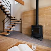 <p> 版築壁: 土を固めて築き上げた版築壁は、幅2700mm×高さ2000mm、厚みも280mmあり、リビングでひときわ存在感を放ちます。昔ながらの工法でつくっているため、外観はまるで地層のようにダイナミックで、大地の力強さと美しさを感じることができます。また、重くて熱容量も大きいため、薪ストーブの背後に配することで、蓄熱装置も兼ねています。夏もひんやり冷たく室温を下げるなど、十分な調湿効果を期待できます </p>