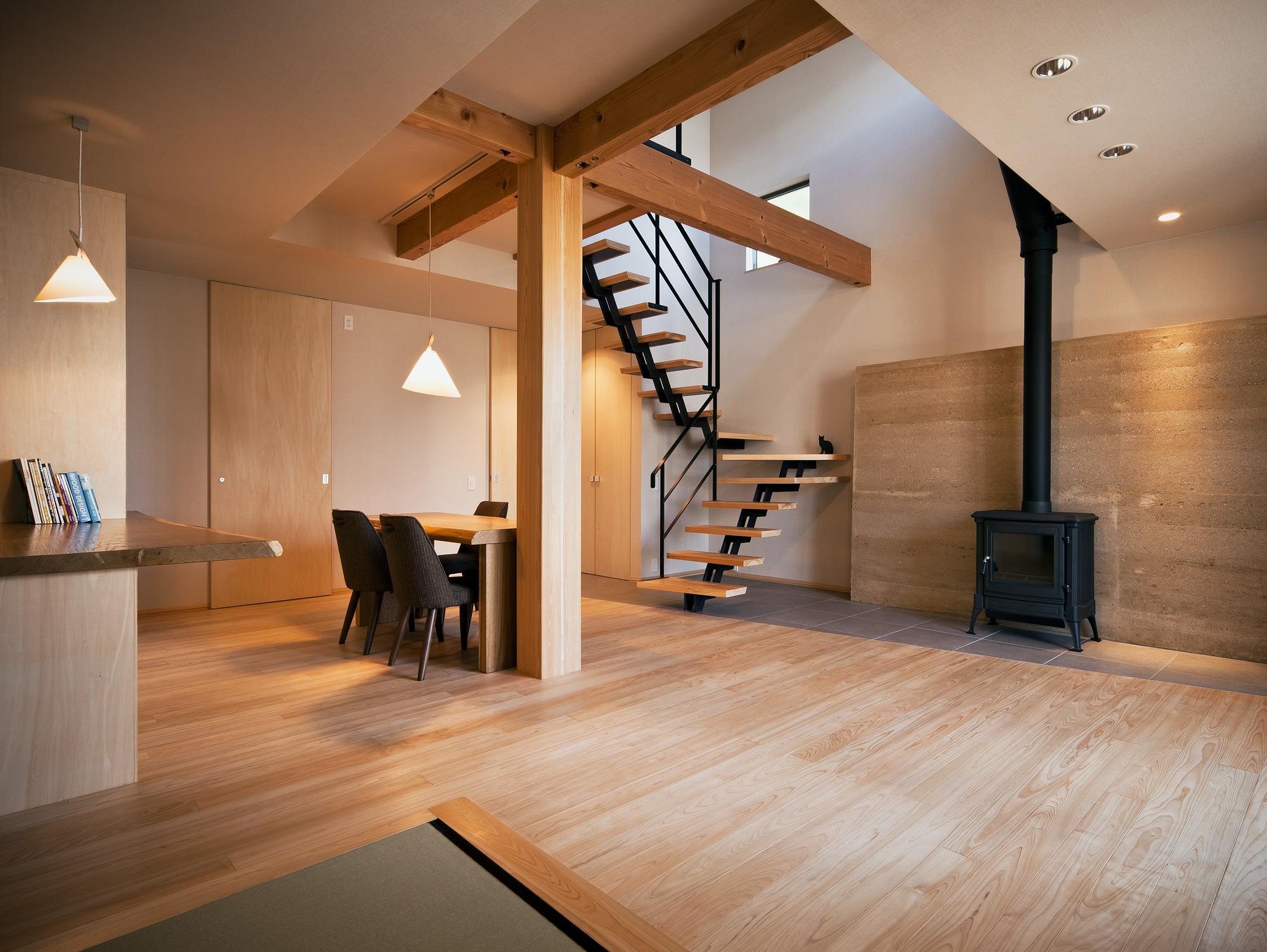 和室よりリビングダイニングを見る: 家の中心には280mm角のどっしりとした大黒柱が鎮座しています。この材木は、材木市場でクライアントと一目ぼれしたものでした。基礎から屋根まで通る、6mの一本もので、決して飾りではなく、家の重心で大黒柱本来の役割を発揮しています。背割りは埋木され、表面は丁寧にきめ細かく仕上げられているため、つい手で触れたくなってしまいます
