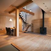 <p> 和室よりリビングダイニングを見る: 家の中心には280mm角のどっしりとした大黒柱が鎮座しています。この材木は、材木市場でクライアントと一目ぼれしたものでした。基礎から屋根まで通る、6mの一本もので、決して飾りではなく、家の重心で大黒柱本来の役割を発揮しています。背割りは埋木され、表面は丁寧にきめ細かく仕上げられているため、つい手で触れたくなってしまいます </p>