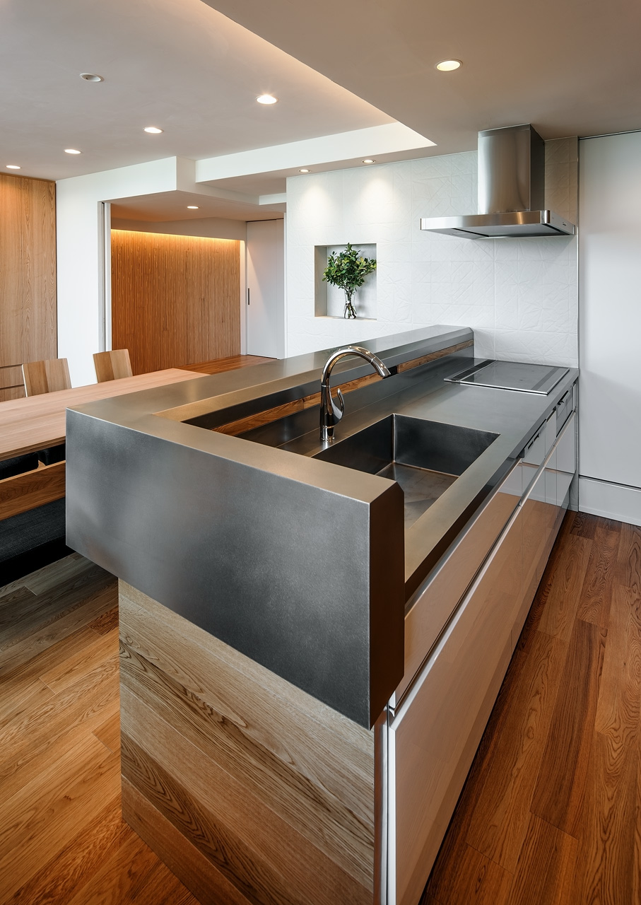 キッチンカウンター: エッジをシャープにし、金属の塊のように見えるデザインをこころがけました