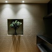 <p> リビングの壁: タイルながら、折り曲げた紙のテクスチャーが堅さのない自然で優しい風合いを空間に与えてくれます。ダウンライトを壁際に配置し、その素材感を強調しています </p>