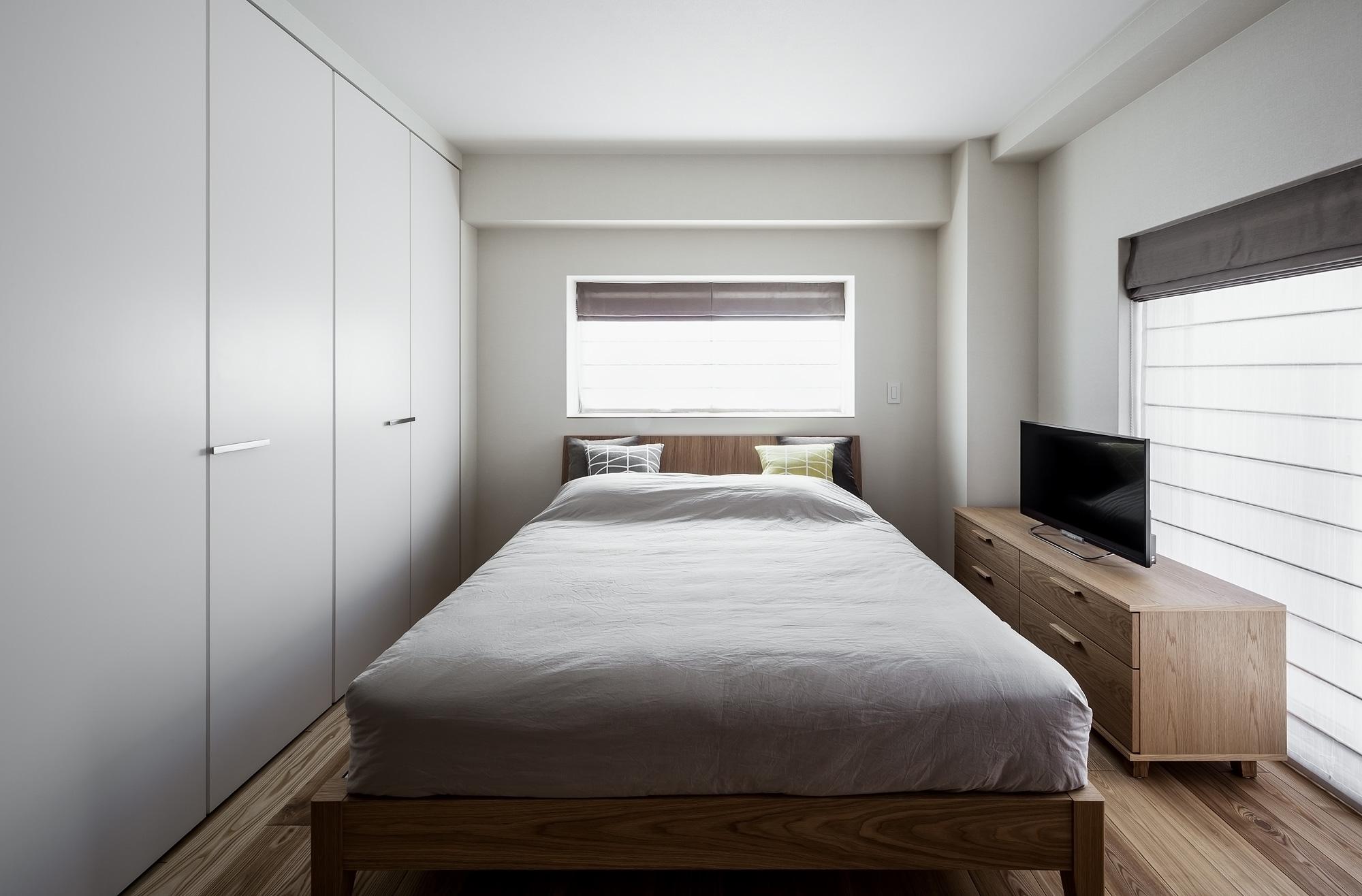 主寝室: 白を基調としたデザイン。収納の扉も白にして、壁のようにみせています