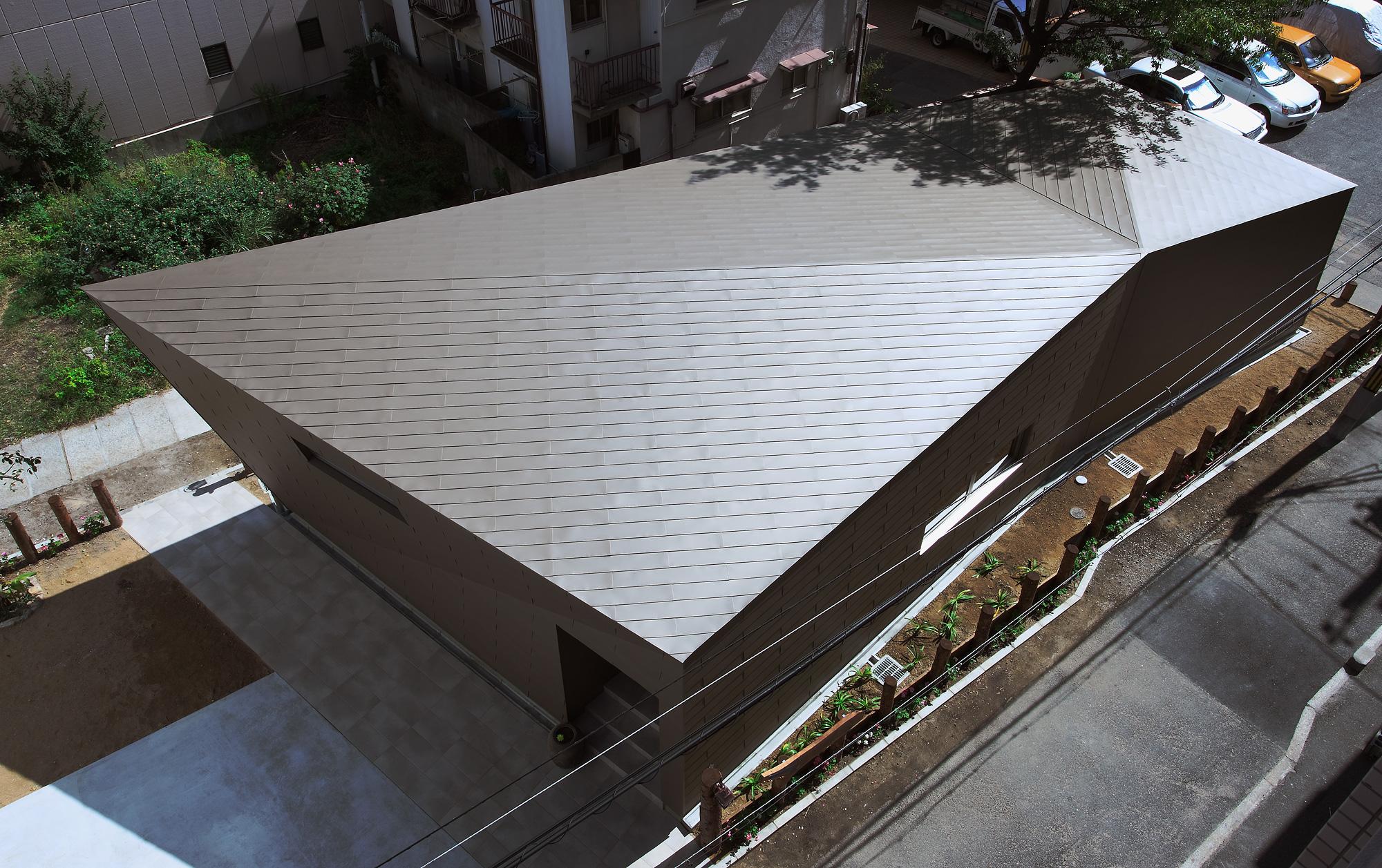 北西からの俯瞰: 屋根と壁は同一素材で、力強いひとつの「塊」を表現しています