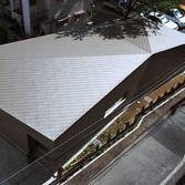 <p> 北西からの俯瞰: 屋根と壁は同一素材で、力強いひとつの「塊」を表現しています </p>