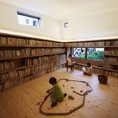 <p> 絵本ルーム: 30年間に収集された5200冊の絵本が壁一面に並びます。照明はモアレ現象を利用したグラフィカルで遊びのあるデザインの間接照明を用いました。子供のスケールに合わせた窓からは緑豊かな空地を望むことができます </p>