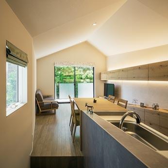<p> キッチンからリビングダイニングをみる: 公園の緑に向かって、床も天井もフレアスカートのように広がっていくデザイン </p>
