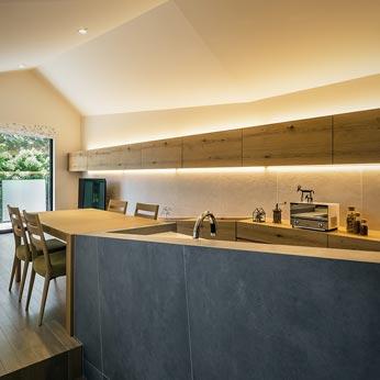 <p> キッチンからリビングダイニングをみる: 切妻の勾配天井が家具に仕込まれた間接照明によって優しく照らされ、温かみと安らぎのある空間に </p>