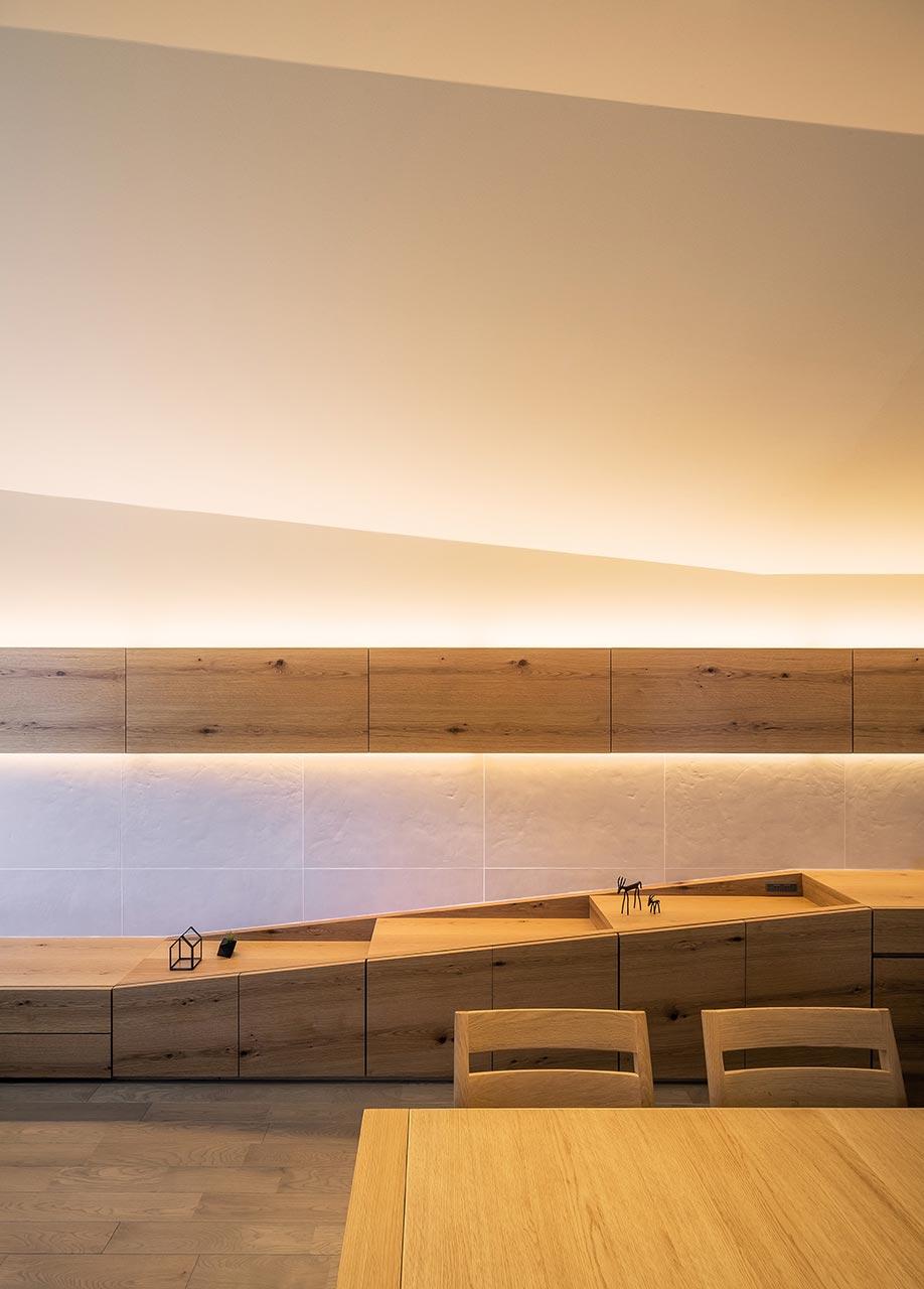 リビングダイニングの壁面: 視覚的により広がりを感じられるよう、壁面の家具の形状も、広がっていく天井のラインに呼応してつくられています