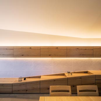 <p> リビングダイニングの壁面: 視覚的により広がりを感じられるよう、壁面の家具の形状も、広がっていく天井のラインに呼応してつくられています </p>