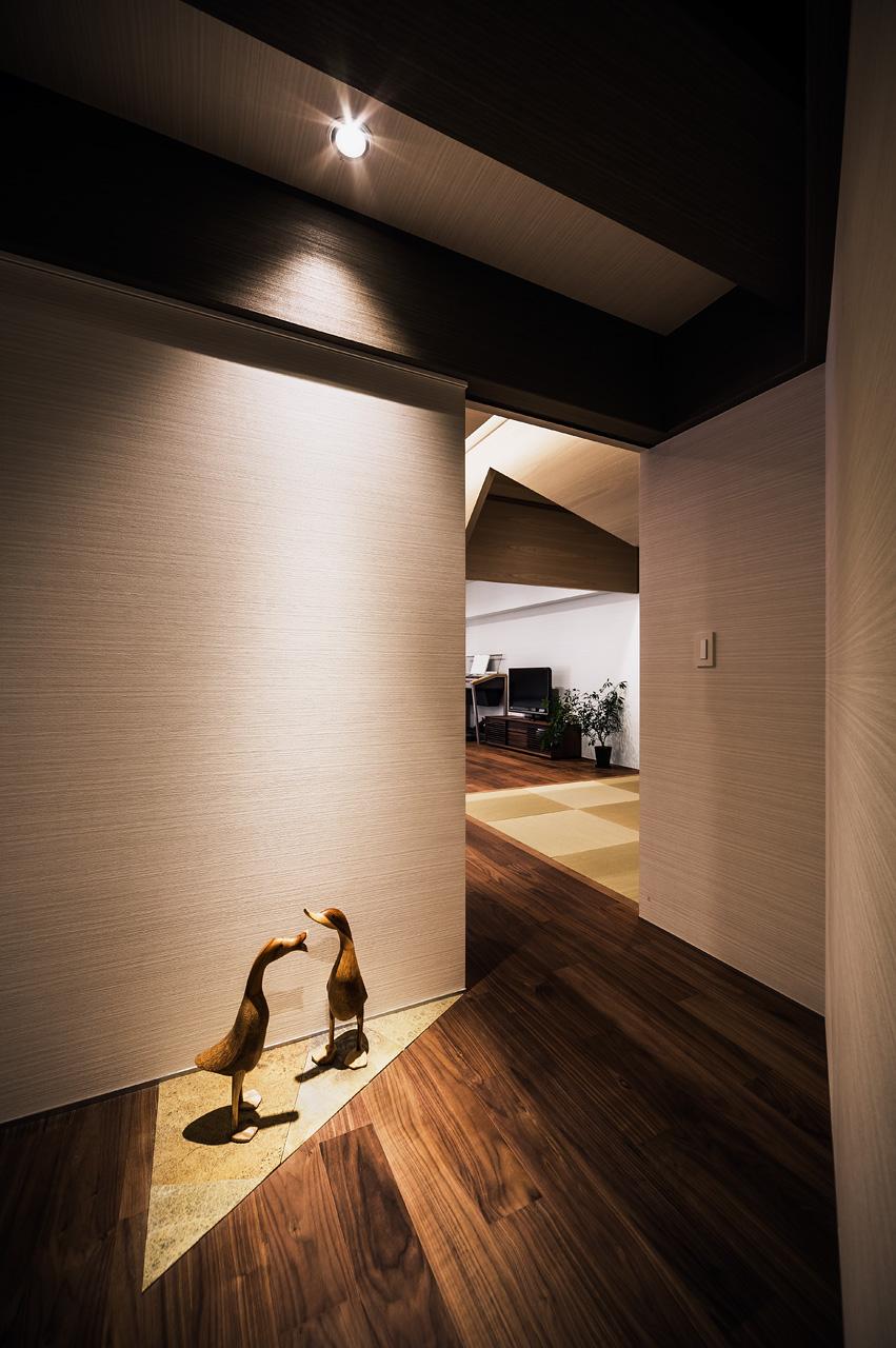 正面外観廊下からリビングルームをみる: 玄関からの廊下をクランクさせ、斜めの動線をつくりました。その先に見える三角の切妻が期待感を高めます。廊下の一部に設えた三角形の天然石貼りの床は、単調な廊下に楽しみと彩りを与えます
