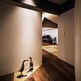 <p> 正面外観廊下からリビングルームをみる: 玄関からの廊下をクランクさせ、斜めの動線をつくりました。その先に見える三角の切妻が期待感を高めます。廊下の一部に設えた三角形の天然石貼りの床は、単調な廊下に楽しみと彩りを与えます </p>