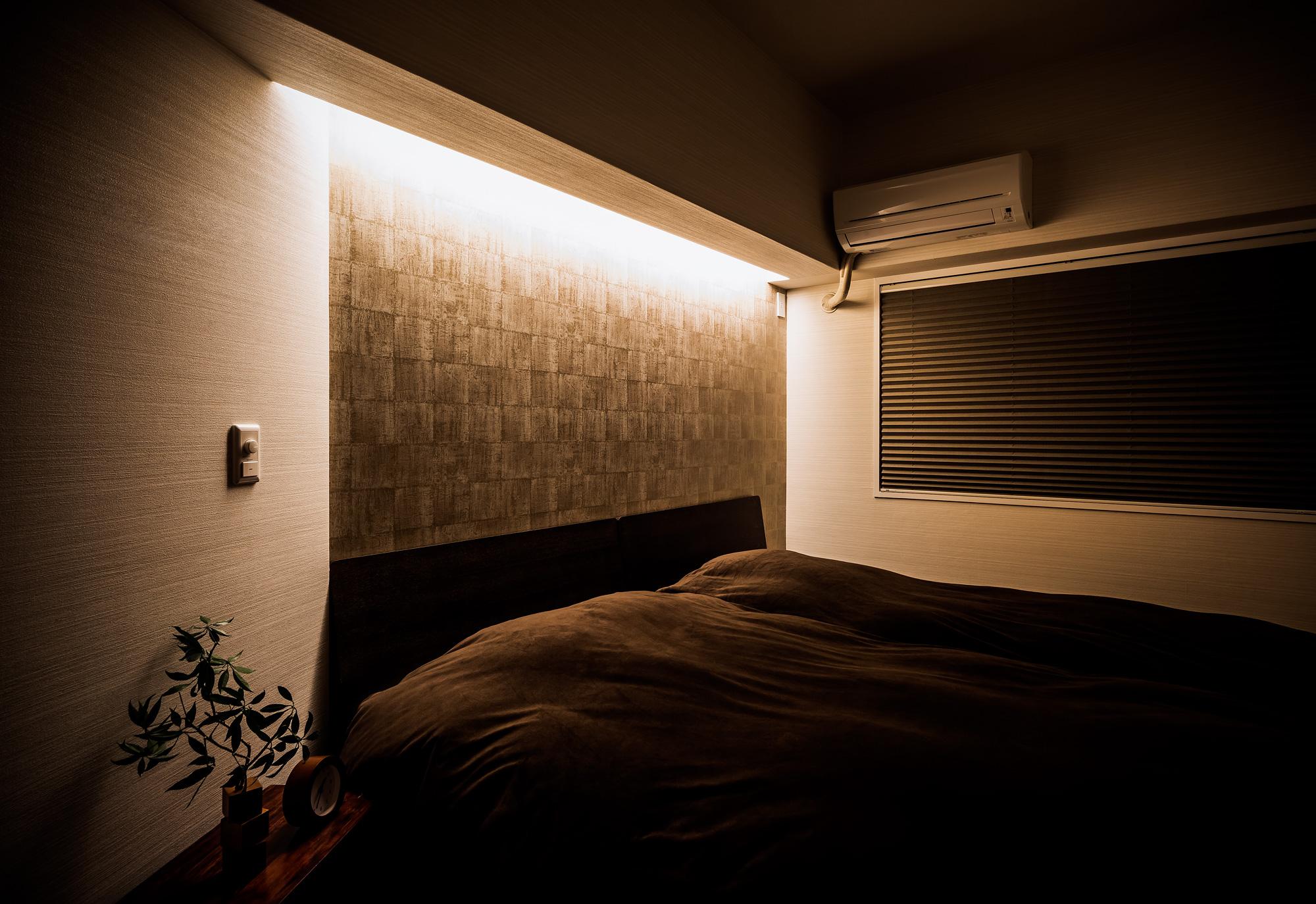 ベッドルーム: 異なる素材を際立たせるために設置した、壁ぎわの間接照明は調光機能つきで、常夜灯の役目も果たします