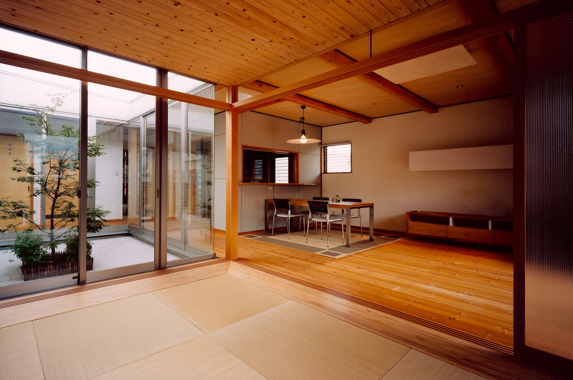 和室よりLDKと中庭を見る: LDKの床は25mm厚のパイン材。針葉樹のフローリングは柔らかい肌触りで暖かみを感じるのが特徴です。床のオイル塗はコストダウンのため、クライアントと設計者でおこないました