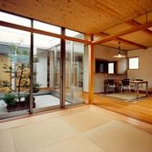 <p> 和室よりLDKと中庭を見る: LDKの床は25mm厚のパイン材。針葉樹のフローリングは柔らかい肌触りで暖かみを感じるのが特徴です。床のオイル塗はコストダウンのため、クライアントと設計者でおこないました </p>