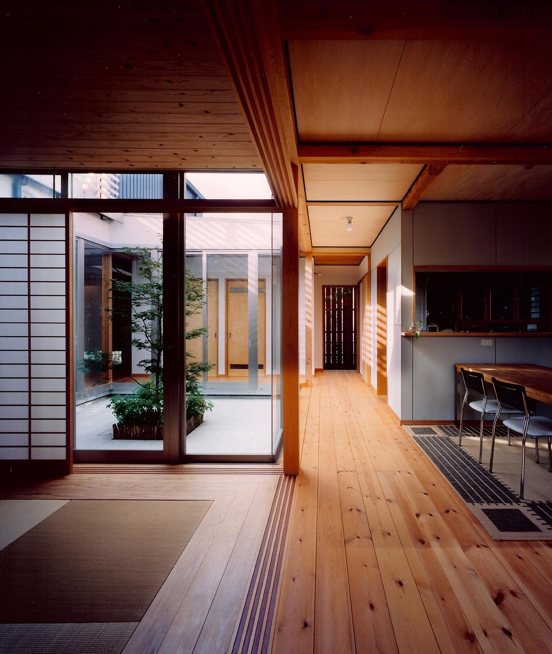 リビングからキッチンと中庭を見る: 中庭に沿った廊下はいつも光に溢れています
