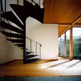 <p> エントランス: 戸をくぐると中庭のノムラモミジ、その奥にLDKを見通すことができます。階段は生活時間の異なる長女の個室に繋がっており、玄関から直接アクセスできるようになっています </p>