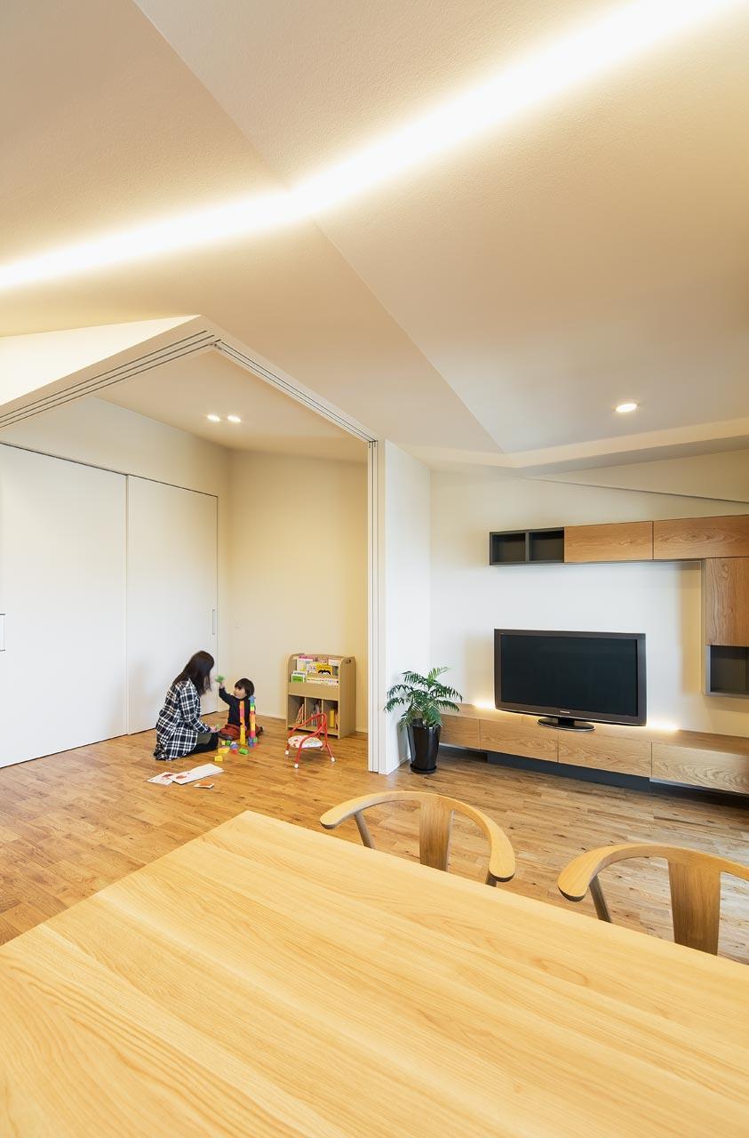 LDKからゲストルームをのぞむ:壁に建具を収納すると、より広い一室空間として使うこともできます。お子さまが成長された後には、主寝室になる予定です