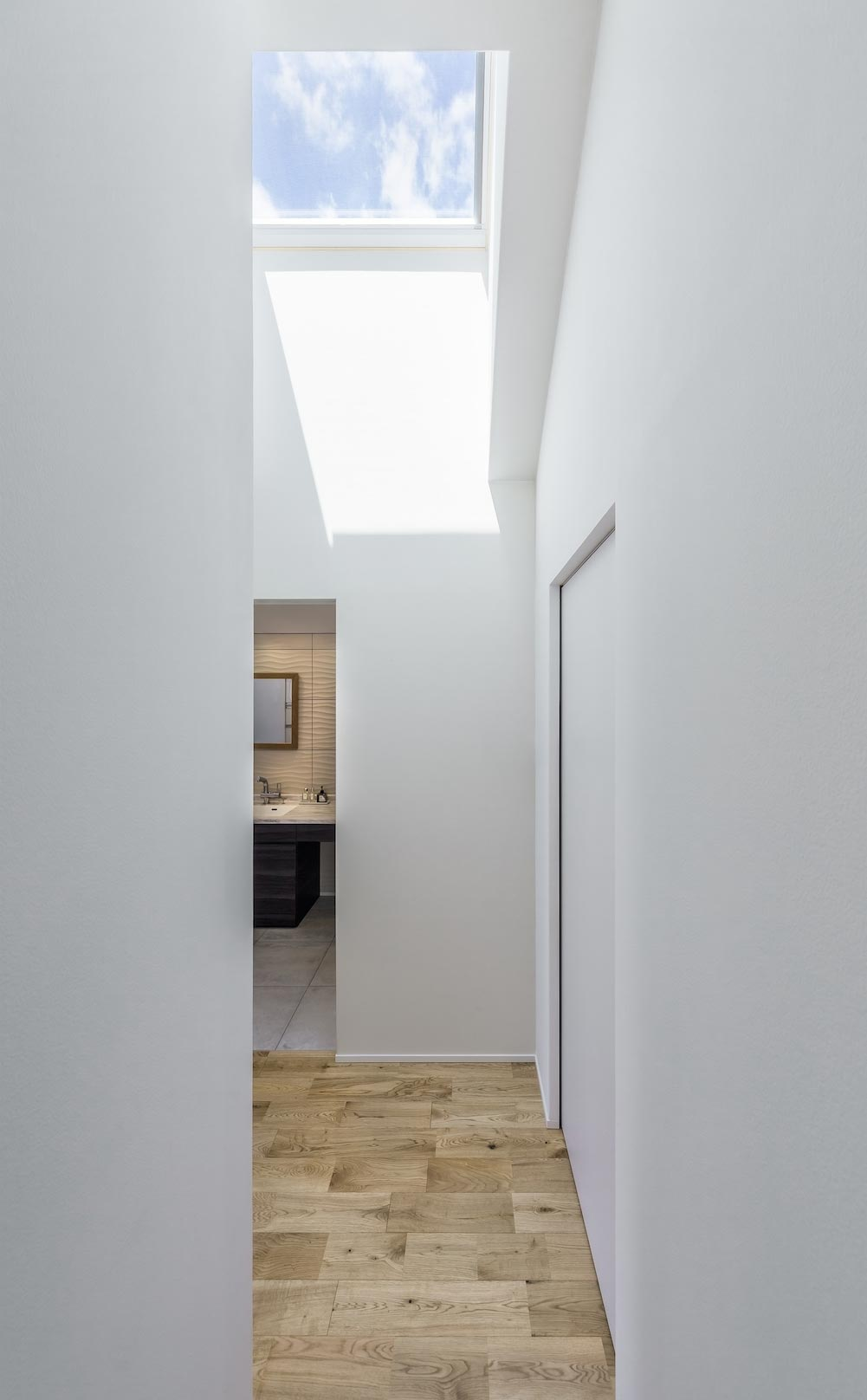 <p> 2F廊下から洗面脱衣室方面をみる: 白い壁とトップライトで明るい印象 </p>