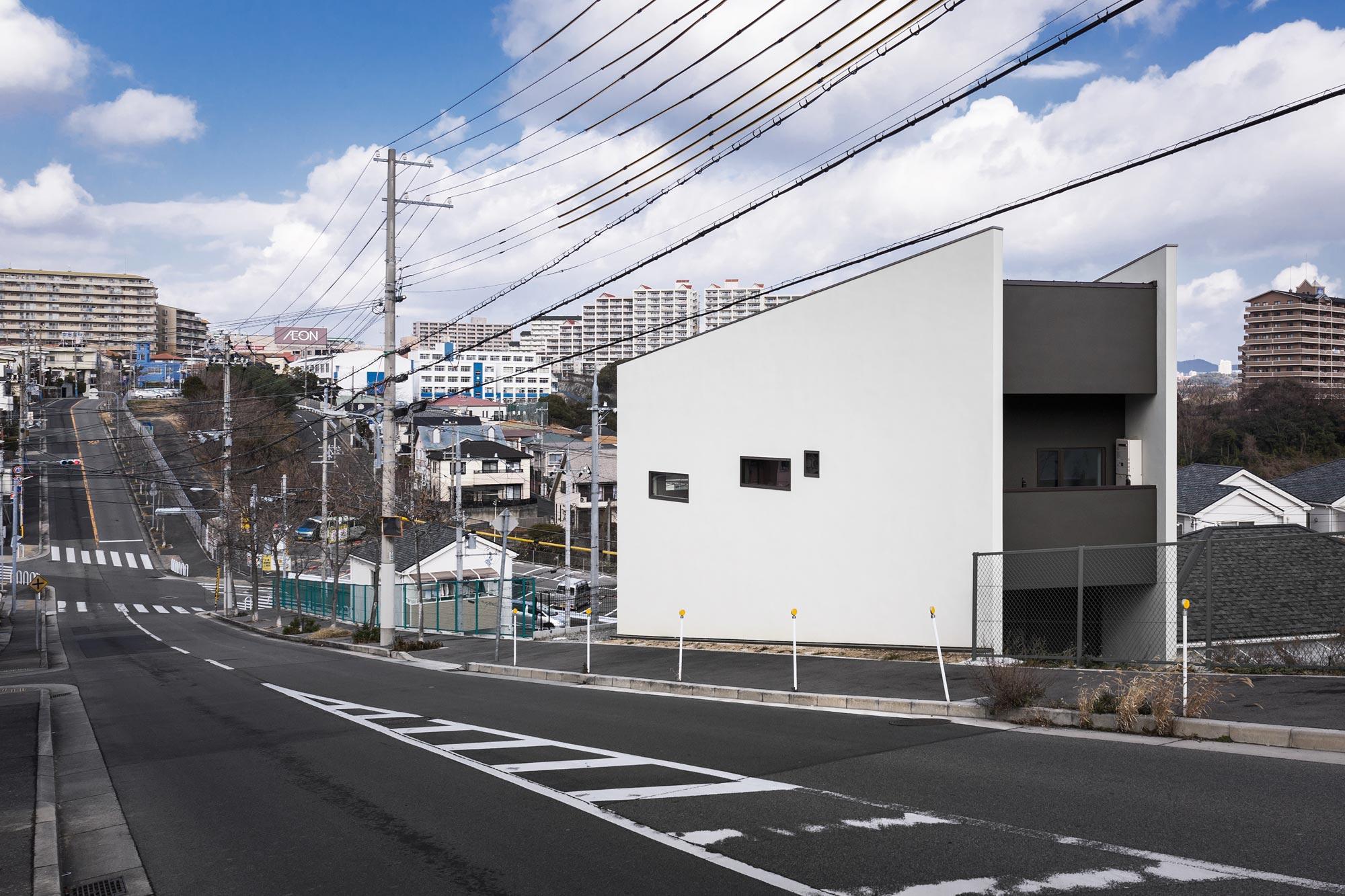 南西より: 高低差が激しい環境です。壁面や開口部は、道路側からの視線をコントロールするデザイン