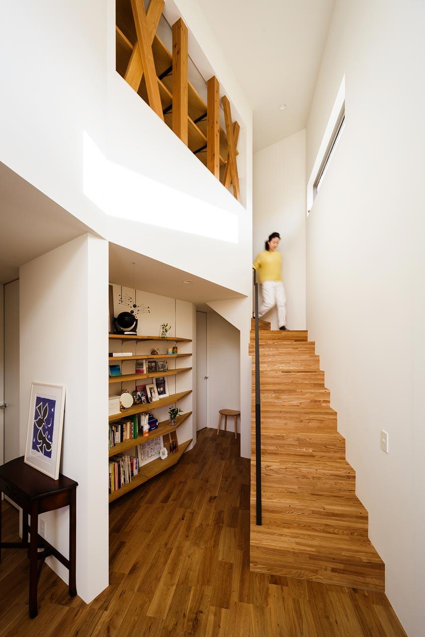 玄関ホール: 吹き抜けで2階LDKまでつながっているため、開放感のある空間です。階段横には、お気に入りのものを飾る棚が。ここへ「オープンに」収納することで、空間に個性がうまれていきます