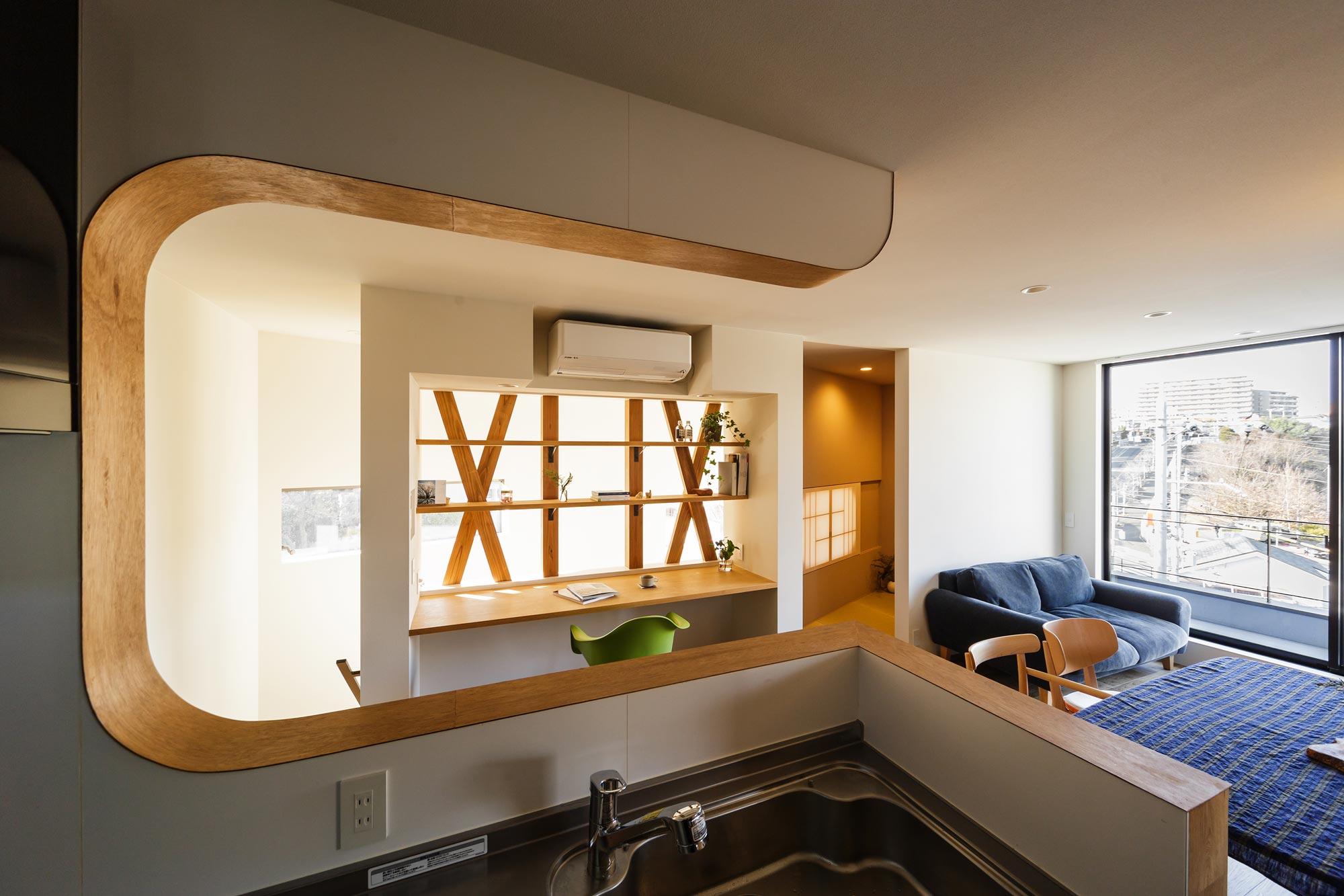 キッチンから書斎・吹き抜け方面をみる: LDKや階下まで、つねに家族の気配を感じながら家事をすることができるキッチンの配置です