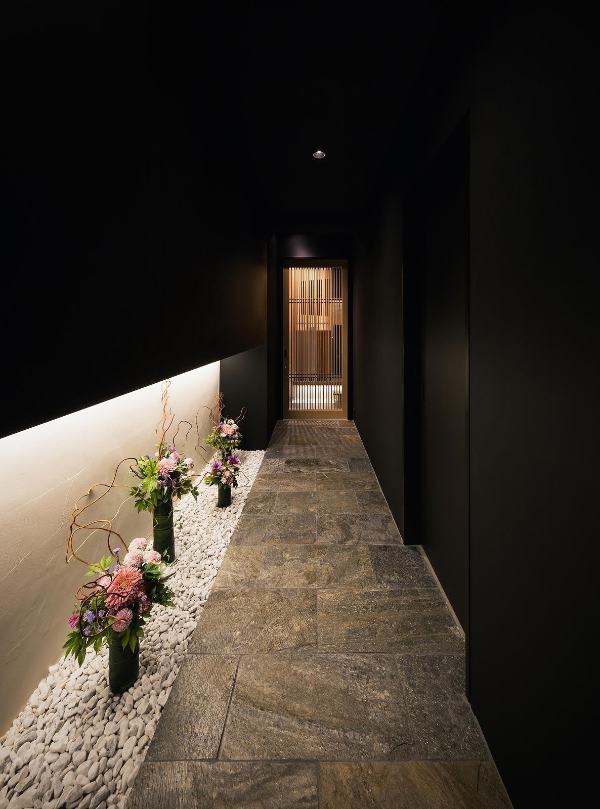 <p> エントランスをくぐり、真っ黒な石畳の露地を抜けて店内へ </p>