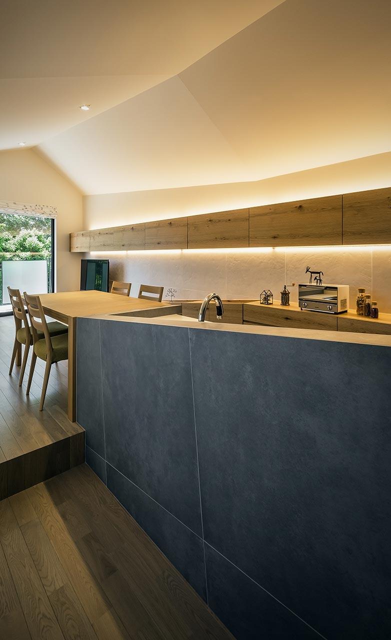 キッチンからリビングダイニングをみる: 切妻の勾配天井が家具に仕込まれた間接照明によって優しく照らされ、温かみと安らぎのある空間に